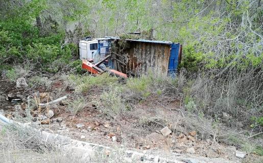 El camión de gran tonelaje recorrió una decena de metros por la pendiente y acabó semivolcado y frenado junto a unos pinos tras sufrir una salida de vía en la carretera de acceso a Cala Tarida.