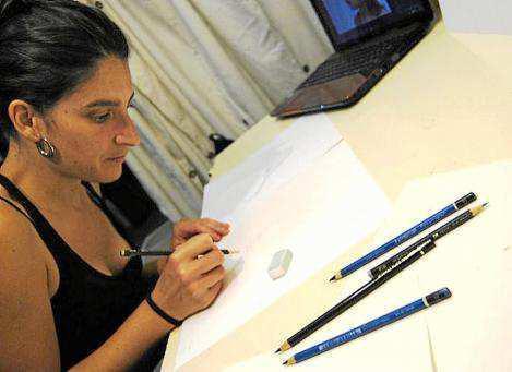 En la imagen superior la artista catalana afincada en Granada María Arjona pintando una de sus obras.