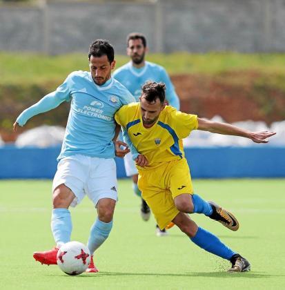 Cirio, delantero de la UD Ibiza, pasa el balón ante la presión de un jugador del Mercadal.