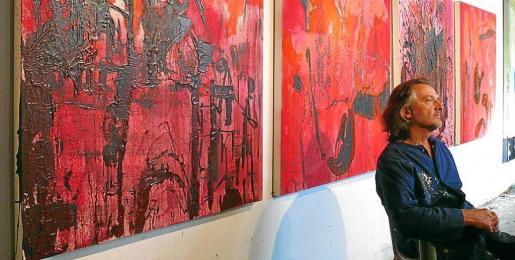 Imagen de archivo del pintor canadiense Michel Beaucage junto a sus obras.