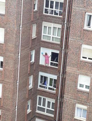 Impresionante imagen de la mujer limpiando las persianas.
