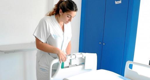 La enfermera Cristina Martín instalando uno de los puntos de lavado de manos en una cama del hospital.