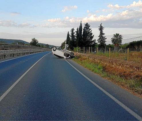 El coche quedó volcado sobre la calzada tras el impacto.