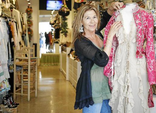 Piluca Bayarri con una de sus prendas en su tienda situada en el carrer de Sa Creu del barrio de la Marina de Ibiza.