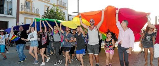 Participantes en la marcha por los derechos LGTBIQ portando una gran bandera arcoiris.
