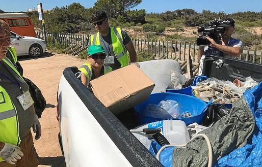 Una de las trabajadoras deposita una caja de residuos en una camioneta.
