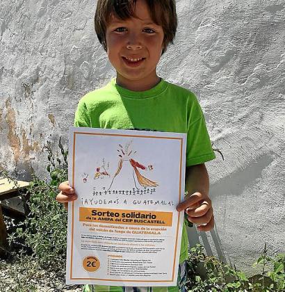 Uno de los niños del centro con el póster del sorteo.