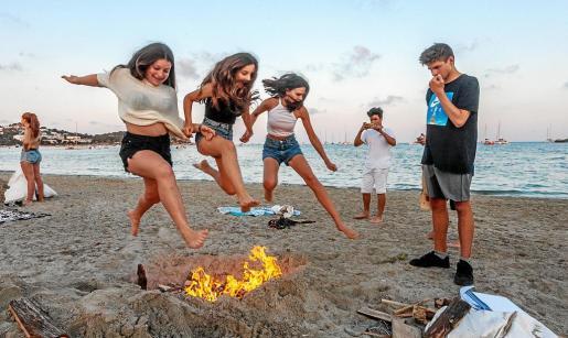 Tres jóvenes saltan uno de los 'foguerons' en la playa de Talamanca.