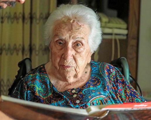 Margalida mira a la cámara tras el álbum de fotos de su centenario.