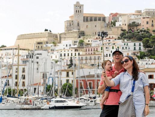 Unos turistas se fotografía en el puerto de Ibiza con Dalt Vila al fondo.