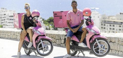 Miguel Tur y una de las repartidoras sentados en las llamativas motos rosas de 'Zas!' en Santa Eulària.