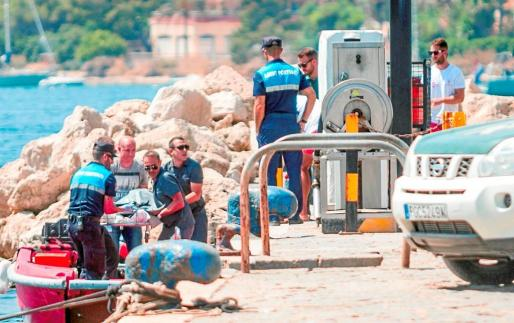 Imagen del momento en el que los agentes y personal del puerto de Sant Antoni trasladaban el cadáver hasta el espigón.