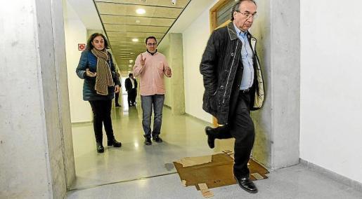 El conseller Martí March en una imagen de archivo sorteando una de las goteras del Conservatorio.