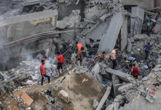 Un grupo de palestinos inspecciona los restos de un centro cultural destruido por un ataque aéreo israelí en Gaza.