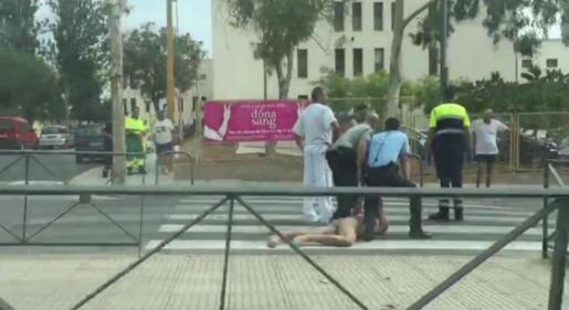 Un agente de seguridad y un policía retienen al hombre después de ser interceptado cuando trataba de huir del hospital.