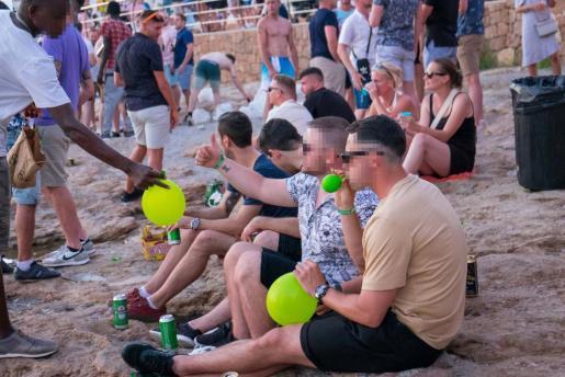 Un vendedor de óxido nitroso entrega tres globos a unos extranjeros que están viendo la puesta de sol.