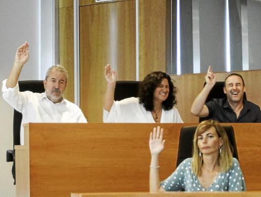 Pepa Marí y Miquel Vericad se ríen durante la votación; el de Guanyem se había despistado mirando el móvil y casi no levanta el brazo. Foto: D. E.
