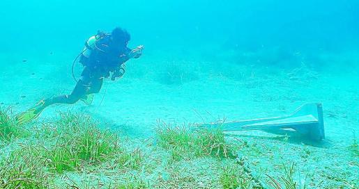 Un submarinista fotografía un ancla sobre la posidonia.