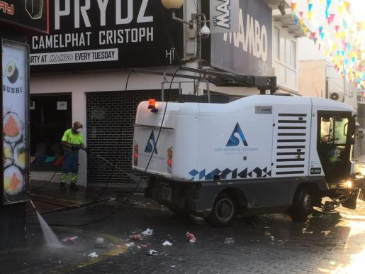 Un camión de limpieza pasa por la calle Santa Agnés junto a dos operarios.