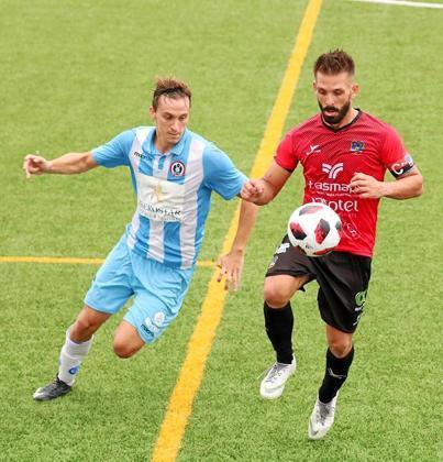 Maikel controla el balón ante la presión de un jugador rival.