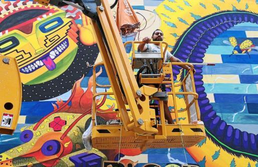 El artista mexicano Spaik ayer por la mañana subido al andamio donde está terminando su trabajo para el CEIP Sa Bodega de Ibiza. Foto: B.I.F.