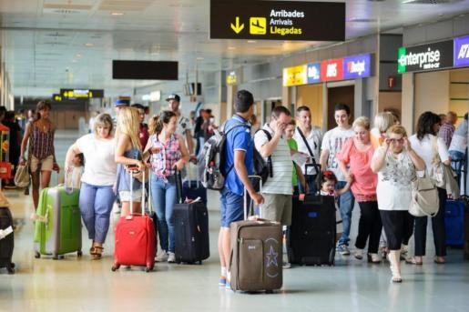 Turistas y residentes ataviados de malestas y equipaje, a su llegada al aeropuerto de Ibiza.