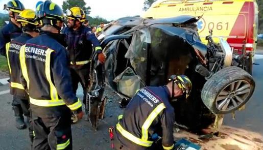 Varios bomberos junto a los restos de vehículo siniestrado.