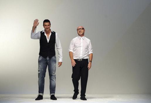 Los diseñadores italianos Stefano Gabbana (i) y Domenico Dolce (d) saludan al público tras presentar su colección Primavera-Verano 2012.