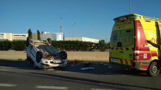 Imagen del coche volcado en la carretera.