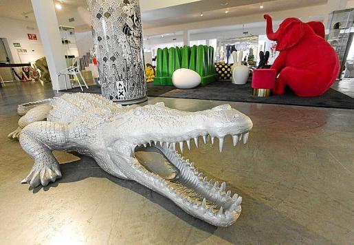 Un cocodrilo a tamaño real y, al fondo, un elefante rojo sentado.
