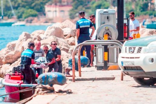Imagen del momento en el que los agentes y personal del puerto de Sant Antoni trasladaban el cadáver de un hombre ahogado el pasado mes de julio.