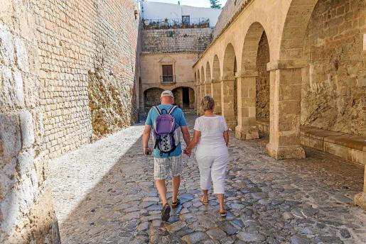 Una pareja de turistas pasea por el Patio de Armas de Dalt Vila.