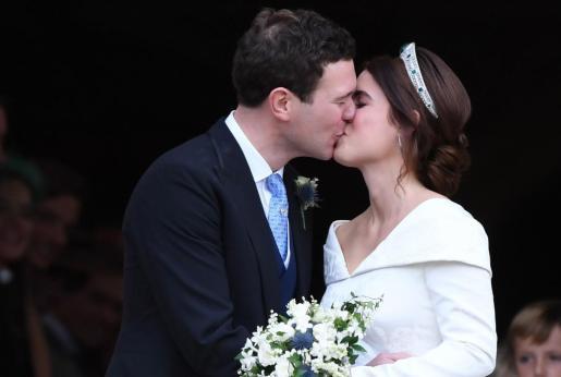 La princesa Eugenia (d) y su marido Jack Brooksbank (i) se besan a su salida de la capilla de San Jorge en Windsor (Reino Unido).