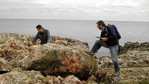 Dos científicos estudiando y analizando otro bloque arrastrado por un antiguo 'tsunami' en Cala Morlanda.