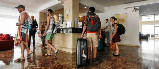 Un grupo de turistas espera su turno en la recepción de un establecimiento hotelero.