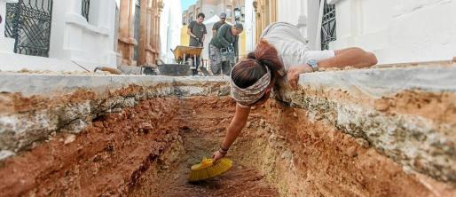 Una trabajadora de la Sociedad Aranzadi limpia el interior de una de las catas realizadas en el pasillo central del Cementeri Vell.