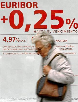 Una mujer pasa bajo la publicidad de una entidad bancaria.