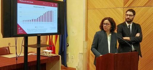 Catalina Cladera y Joan Carrió muestran un gráfico con la previsión de rebaja de deuda que no se cumplirá.