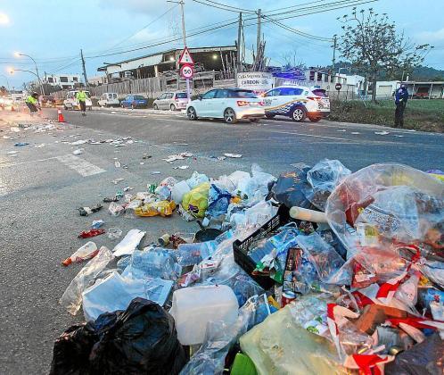 Imagen del rastro de bolsas de basura a lo largo de la carretera y el trabajo de los operarios para limpiar la calzada
