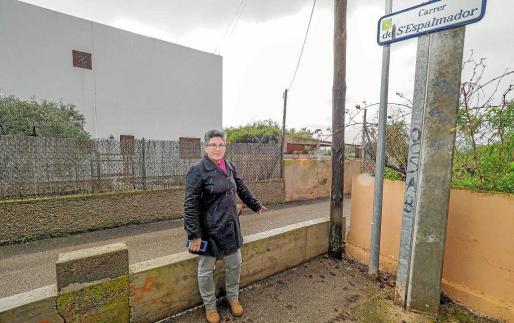 Juana Costa señala el muro que bloquea el final de la calle s'Espalmador en la que vive desde hace más de 50 años.