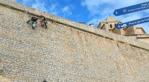 Dos trabajadores se encargan de reponer el mortero de las juntas de la muralla.