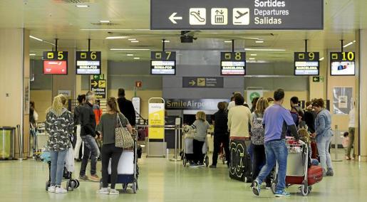Imagen de archivo de varios pasajeros esperando para facturar sus maletas.