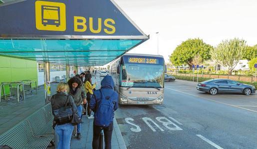 Turistas y residentes esperando en la parada de autobuses del aeropuerto ayer por la mañana.