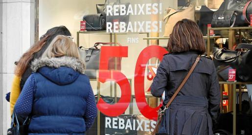 Varias mujeres paradas frente al escaparate de una tienda de complementos ayer, primer día oficial de rebajas en Balears.