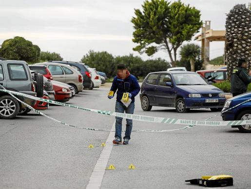 Un agente de la Guardia Civil marca varios puntos en el escenario donde acabó malherido la víctima.