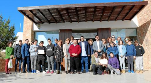 Foto compuesta de los representantes institucionales y de los centros premiados, el CEIP Puig d'en Valls, el IES Algarb y el CEIP Santa Gertrudis, frente al Centre d'Interpretació des Amunts.