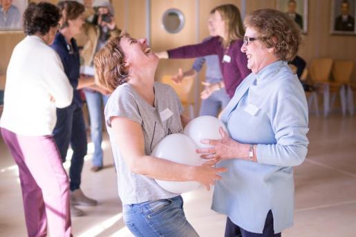 Dos mujeres sonríen durante un ejercicio del taller de risoterapia.