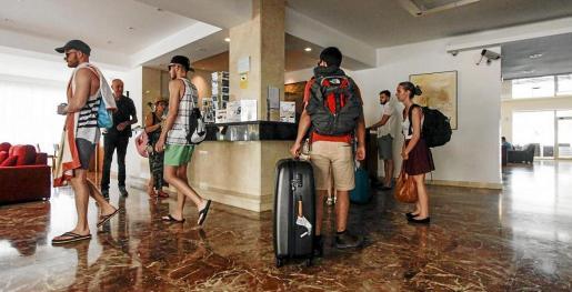 Varios turistas esperan para registrarse en la recepción de un establecimiento turístico de la isla de Ibiza.