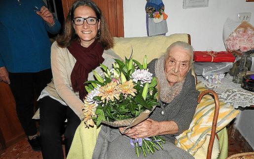 A la izquierda la consellera Vanessa Parellada junto a Catalina Torres Ferrer y su ramo de flores