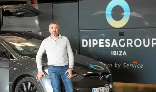 Emilio Díaz posa sobre un coche Tesla y frente a uno de sus autocares, pero reivindica que su fuerte es el servicio.